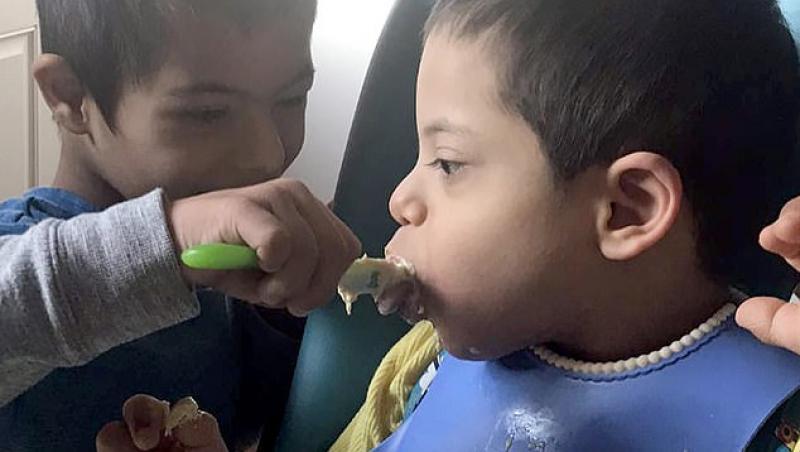 La patru ani, suferă de sindromul Down, dar își hrănește și îmbracă frățiorii paralizați: