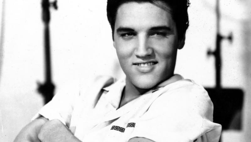Elvis Preasley este așezat pe scaun și zâmbește