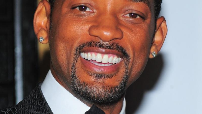 Will Smith, îmbrăcat la costum, afișând un zâmbet larg pe față