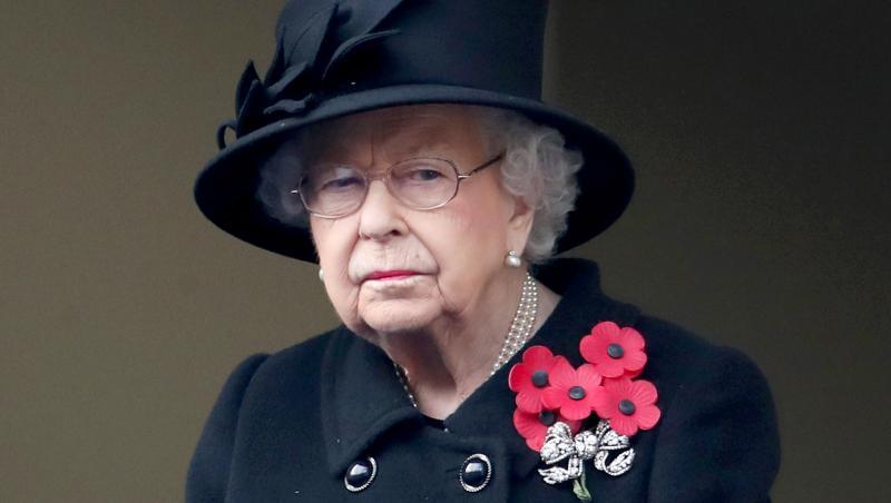Regina Elisabeta a Marii Britanii, purtând o pălărie și o haină negre și o broșă cu flori