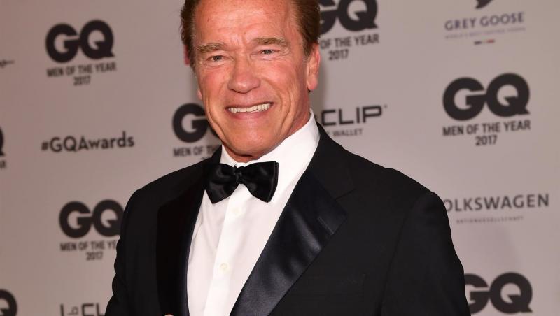Arnold Schwarzenegger imbracat intr-un costum negru, cu camasa alba si papion negru. Zambeste, se uita la camera si isi arata degetul mare.