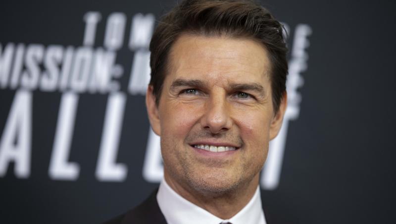 Tom Cruise pe covorul rosu, intr-un costum negru si camasa alba