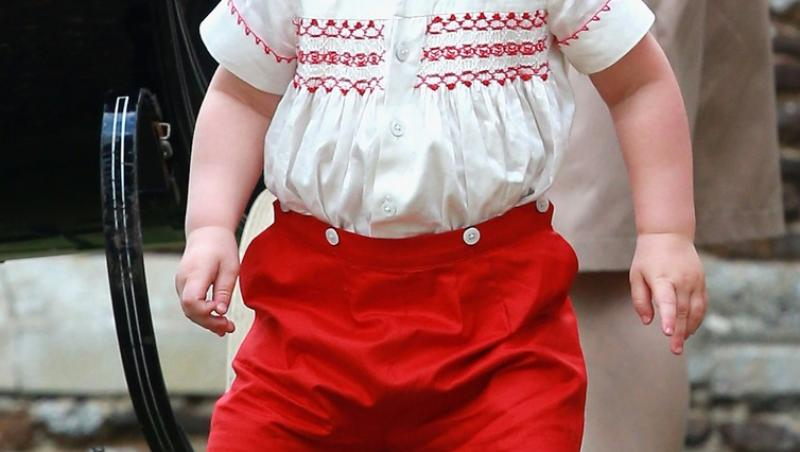Printul George, imbracat intr-o pereche de pantaloni rosii și o bluza alba