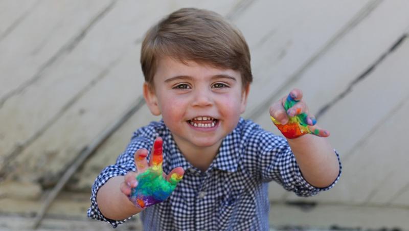 Printul Louis, in timp ce zambeste spre camera foto, cu mainile pline de acuarele colorate