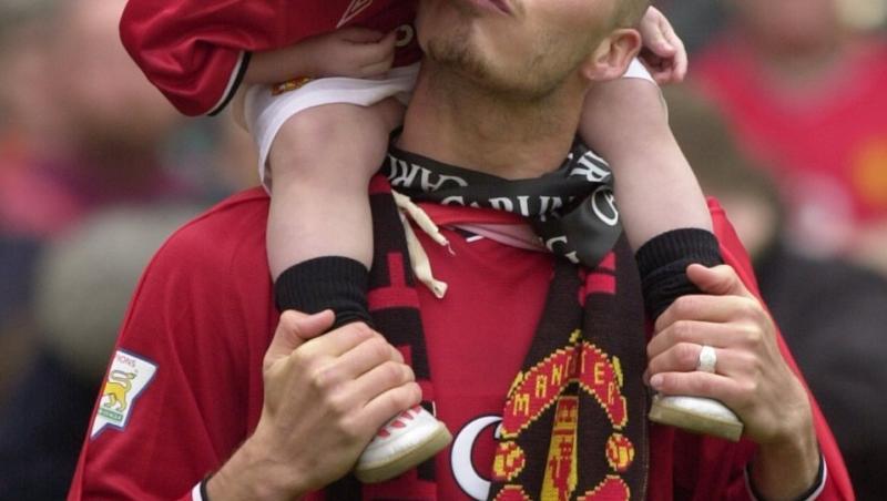 David Beckham, pe terenul de fotbal, cu fiul sau pe umeri, uniforma rosie