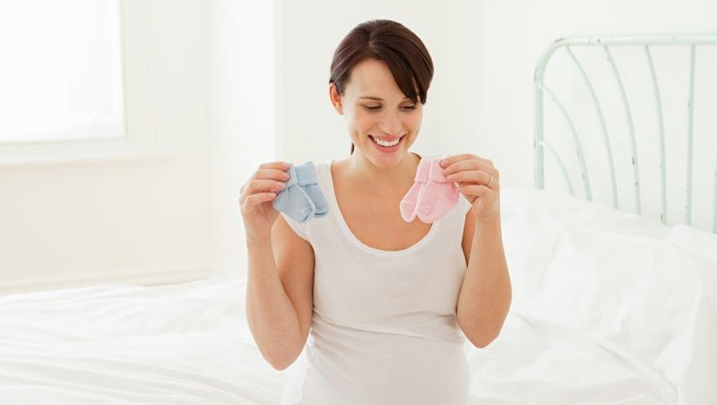 femeie insarcinata imbracata in alb tinand in maini sosete de bebelusi albastre si roz