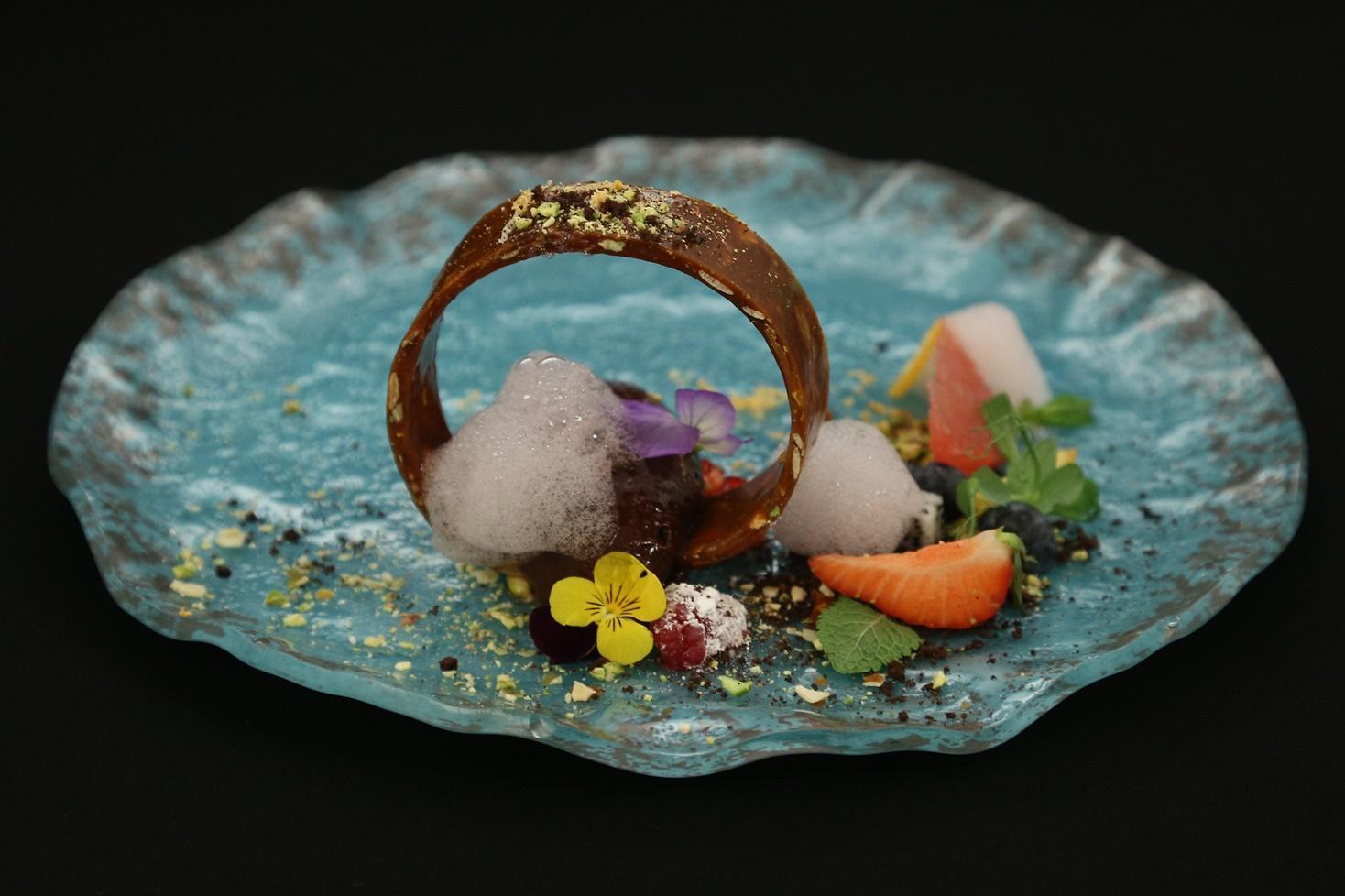 Spumă de nougat cu pământ de ciocolată, fructe, brittle de caramel cu fistic și semințe