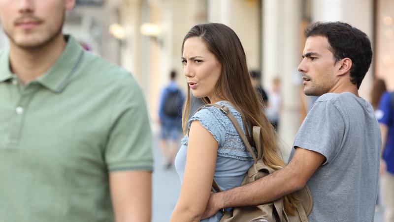 cuplu care merge pe strada si femeia isi intoarce capul dupa un alt barbat