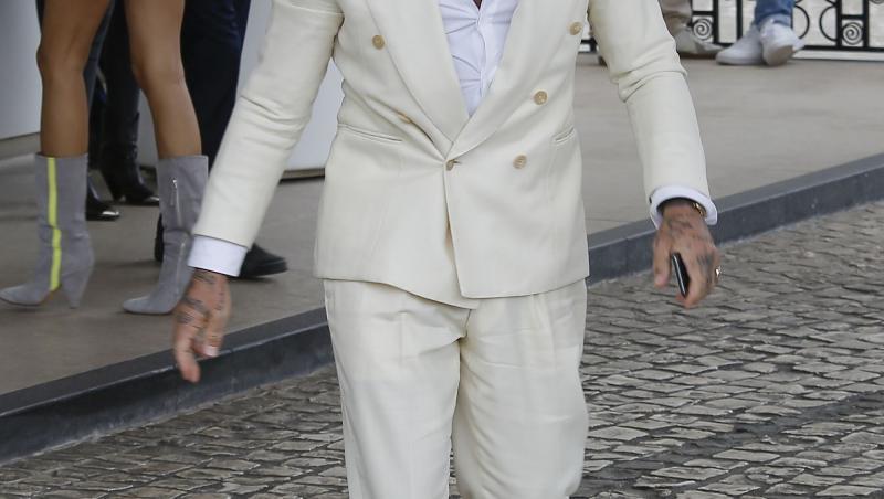Gianluca vacchi, imbracat intr-un costum alb, fotografiat cand merge