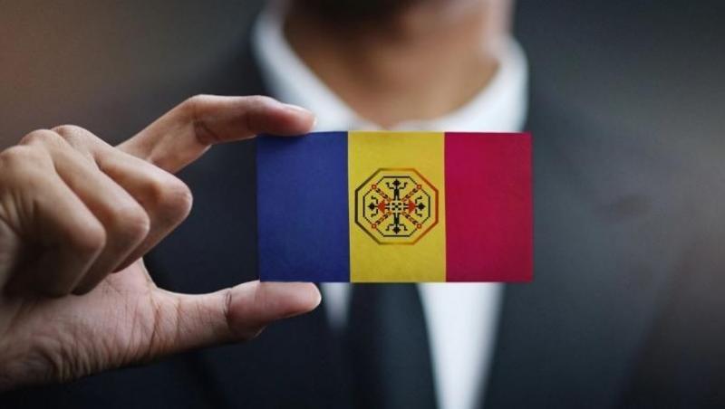 Poză ilustrativă cu mâna unui bărbat ținând între degete un steag al României în miniatură