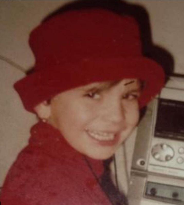 Laura Giurcanu, in copilarie, fotografiata cand poarta o bluza rosie si o palarie in aceeasi culoare