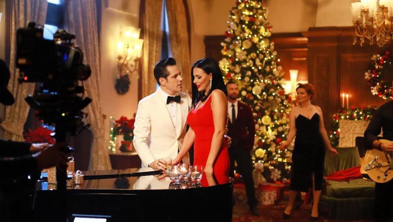 Lavinia Pîrva și Ștefan Bănică lângă pian, iar în spate au un brad de Crăciun