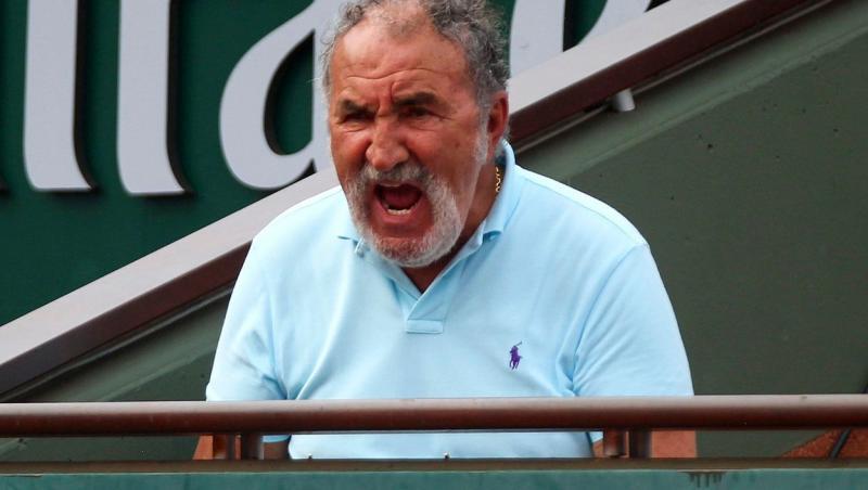 Ion Țiriac, într-un tricou albastru, privind spre terneul de tenis