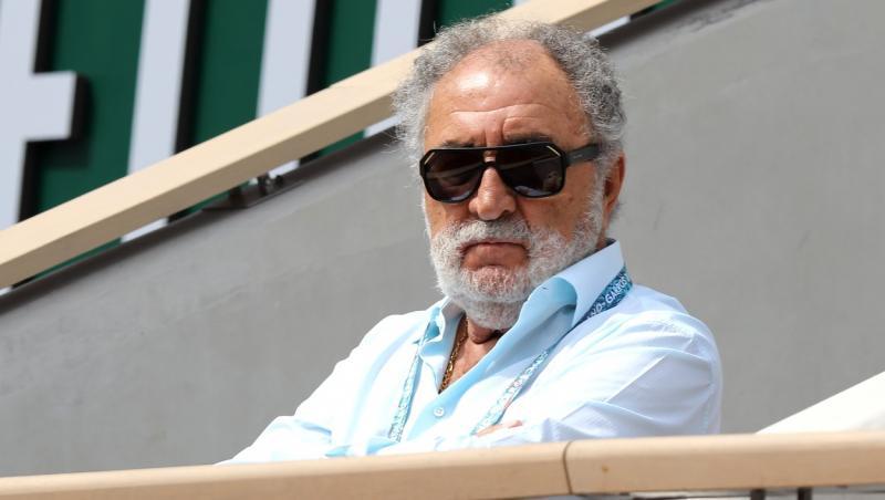 Ion Țiriac, într-o cămașă albastră, privind spre terneul de tenis