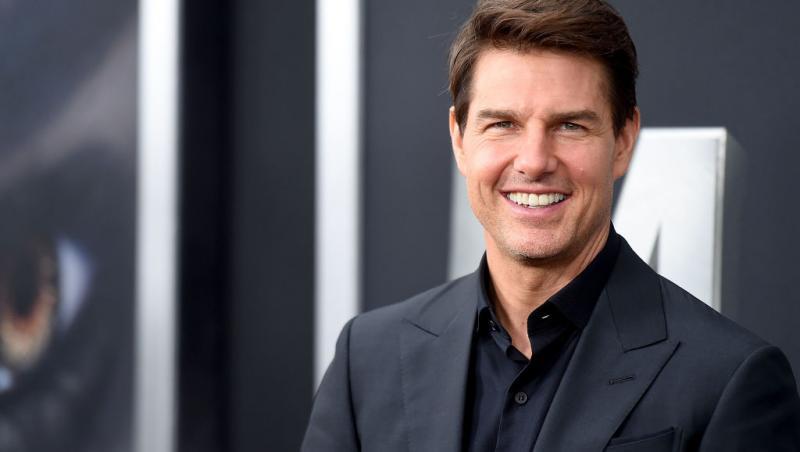 Tom Cruise, imbracat la costum, zambitor