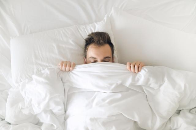 barbat dormind intr-un pat alb