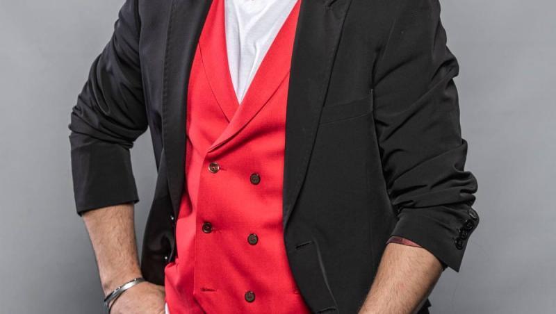 liviu varciu cu un tricou alb, vesta rosie si sacou negru