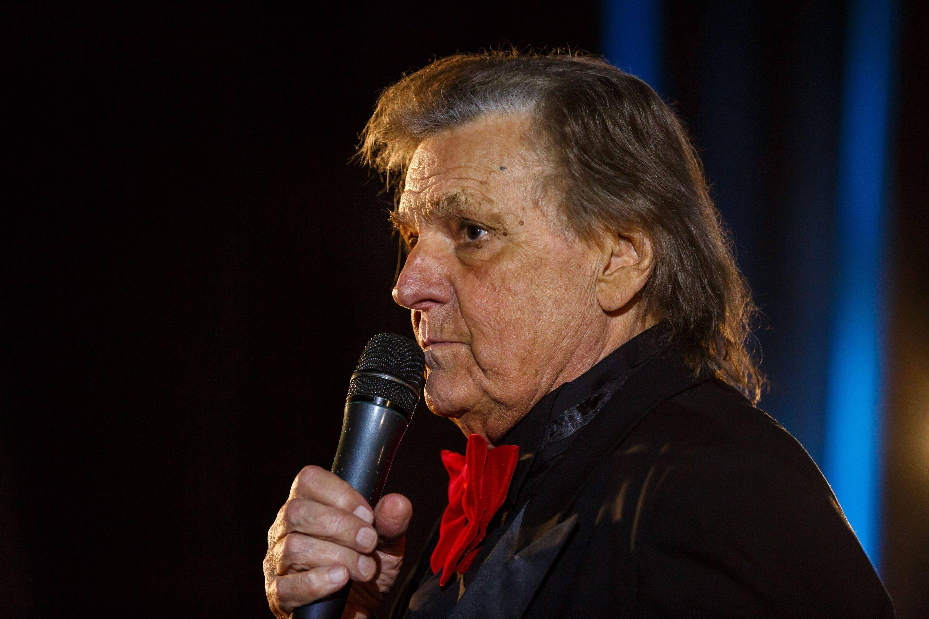 Florin Piersic, pe scenă, purtând o haină neagră