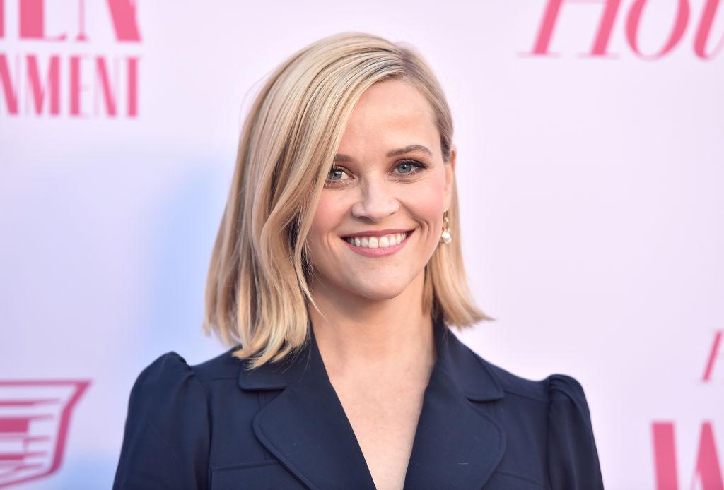 Reese Witherspoon, îmbrăcată într-o rochie albastră, zâmbește când este fotografiată