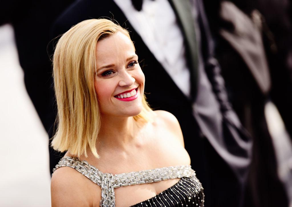 Reese Witherspoon îmbrăcată într-o rochie, cu părul desfăcut, râde