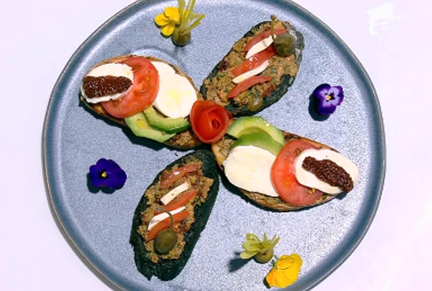 Bruschete cu pastă de măsline și salată caprese pe un platou albastru