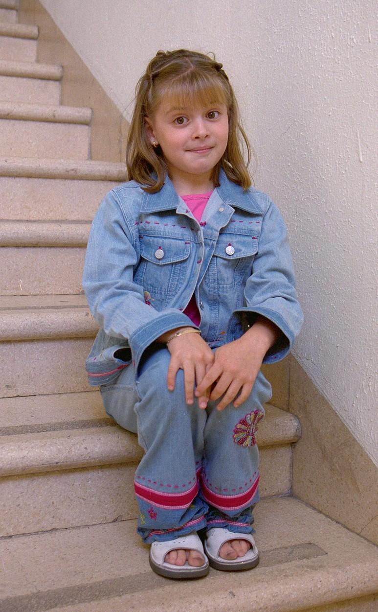 Daniela Aedo, când era doar o fetiță, îmbrăcată în albastru, așezată pe scări