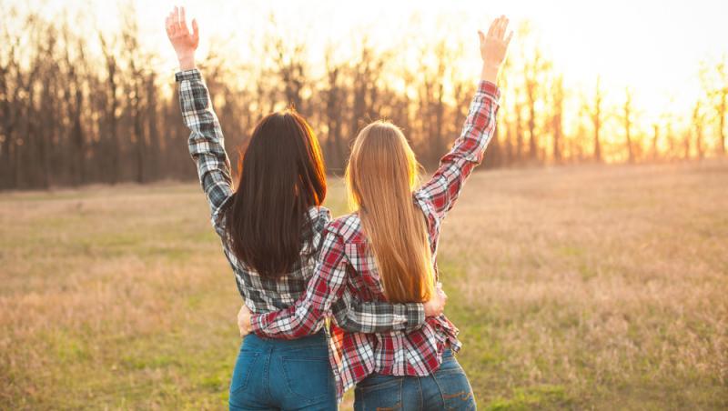 doua femei care stau cu spatele pe un camp cu iarba verde