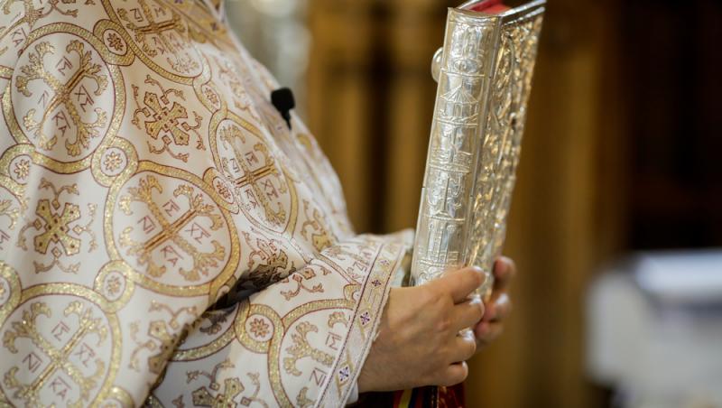 preot care tine in mana cartea sfanta