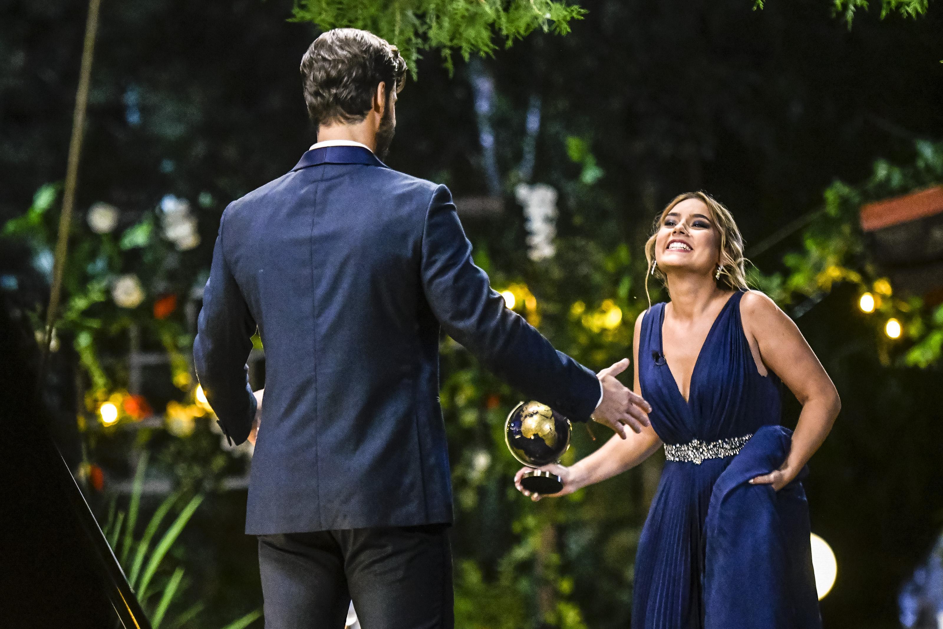 alexandra mucea imbracata intr-o rochie albastra si andi constantin cu spatele