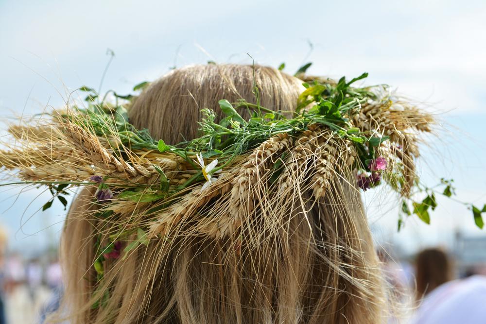 capul unei fete pe care sta o cununa cu flori de sanziene 2021