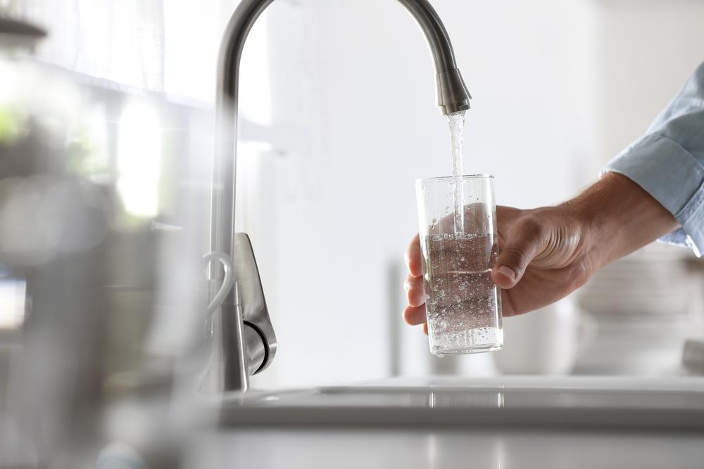 mana unui barbat care umple un pahar cu apa