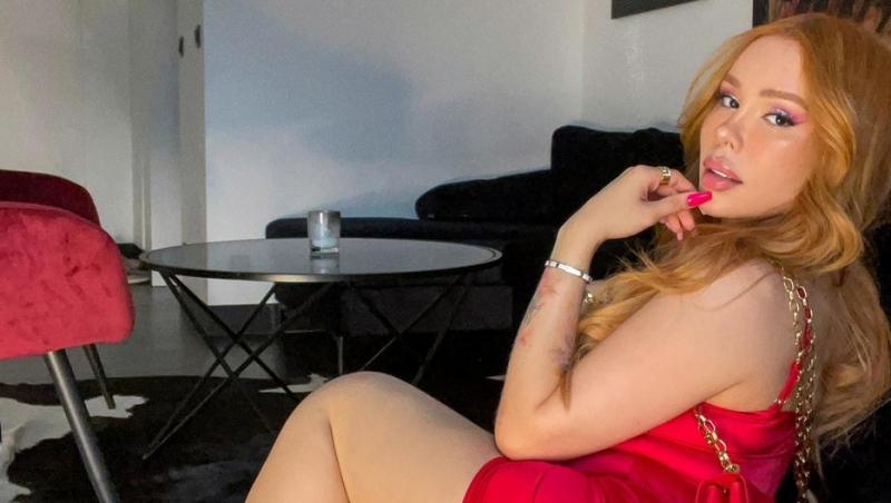 Maria Viera, îmbrăcată într-o rochie sexy, roșie, stă întoarsă într-o parte către fotograf