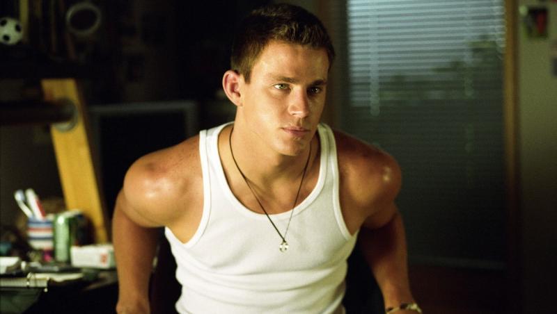 Channing Tatum, îmbrăcat într-un maiou, privește în lateralul aparatului foto