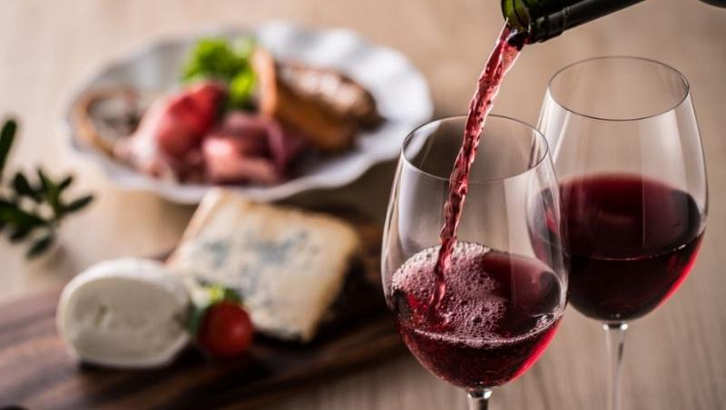 Preparate delicioase și vin roșu turnat în pahar, în prim plan