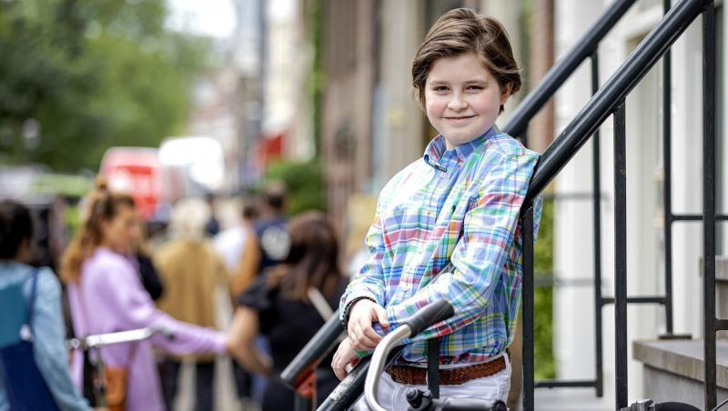 Laurent Simons, afară, îmbrăcat într-o cămașă colorată și pantaloni, zâmbește