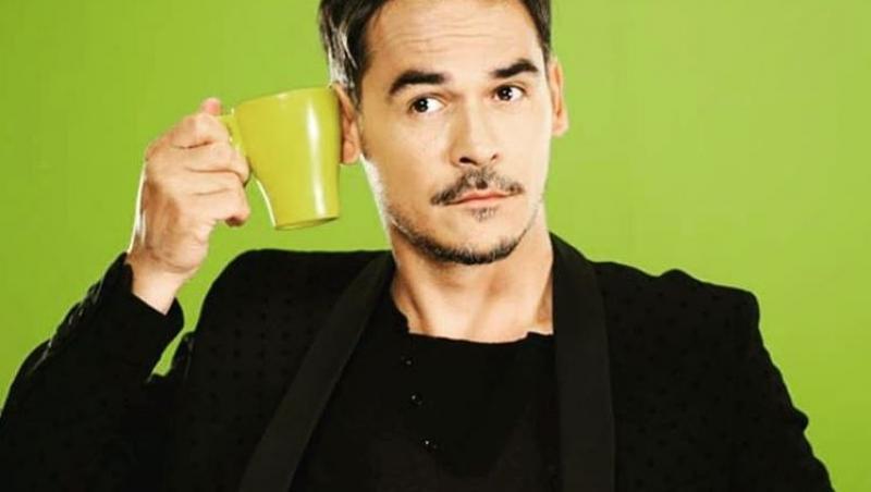 razvan simion intr-un costum negru, cu o cana de cafea verde in mana