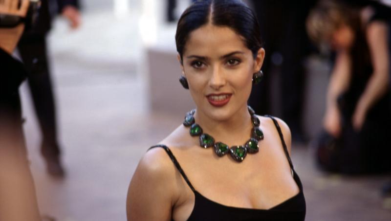 salma hayek in tinerete intr-o rochie neagra cu bretele subtiri si un colier negru cu cercei asortati