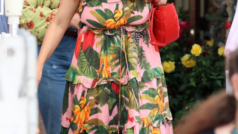 salma hayek intr-o rochie lunga inflorata, cu masca de protectie, ochelari de soare, geanta rosie, pe strada