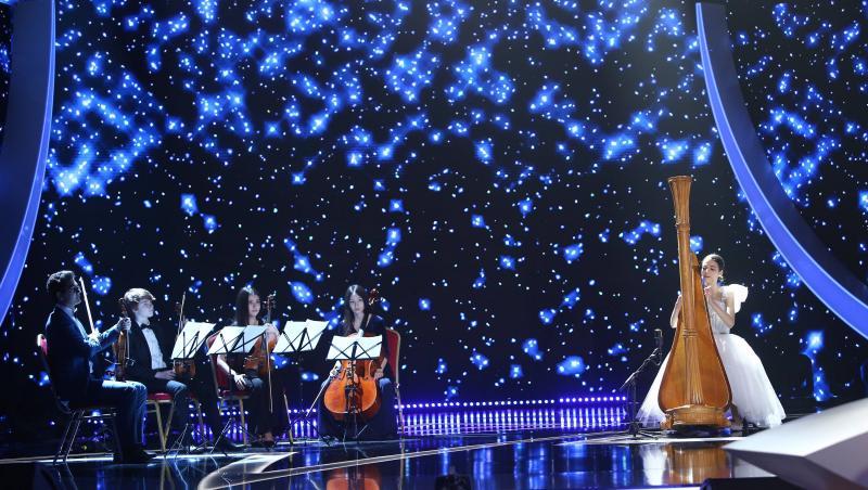 maria ene pe scena la next star intr-o rochie alba cantand la harpa, alaturi de orchestra