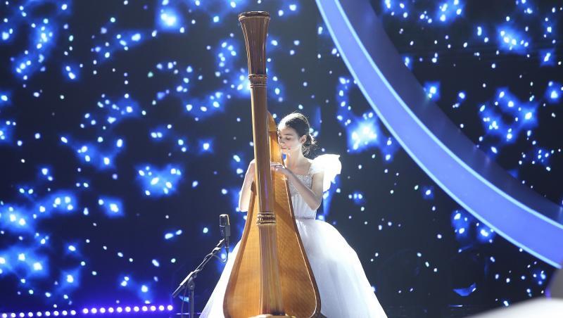 maria ene pe scena la next star intr-o rochie alba cantand la harpa
