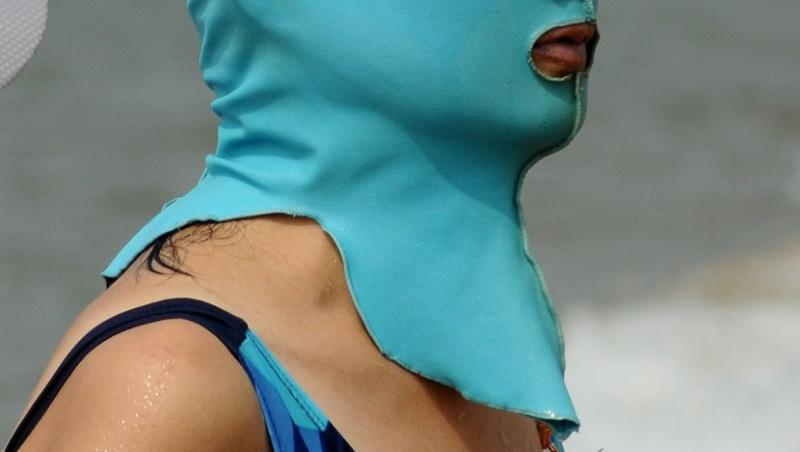 Femeie purtând o mască Facekini bleu, îmbrăcată în costum de baie