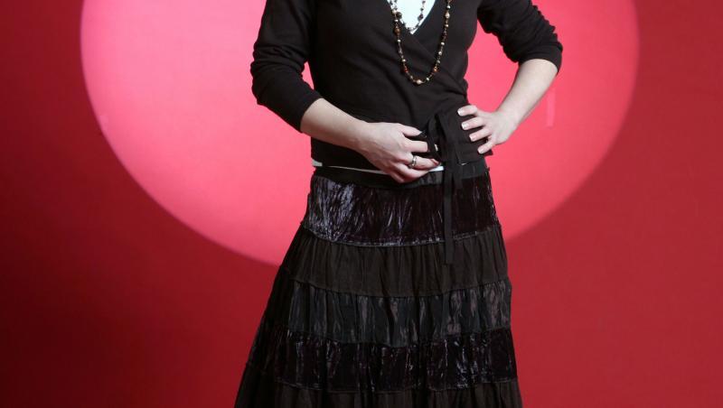 luminita anghel intr-o rochie neagra, lunga, cu maneca lunga, intr-un fundal rosu