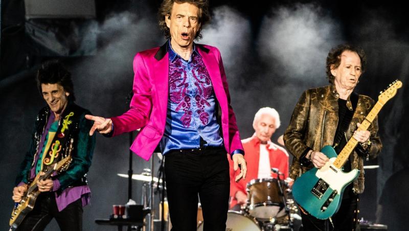mick jagger pe scena alaturi trupa the rolling stones, intr-o camasa albastra, pantaloni negri si sacou roz