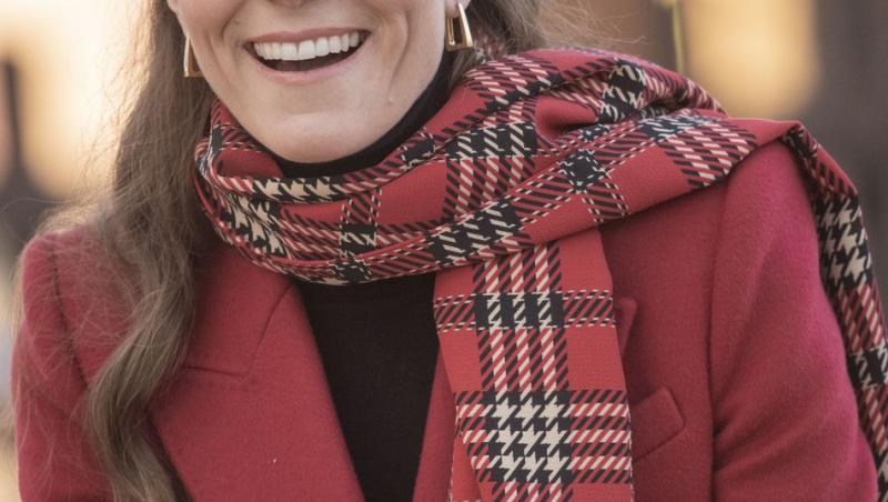 kate middleton cu o bluza neagra, palton rosu si un fular in carouri cu rosu
