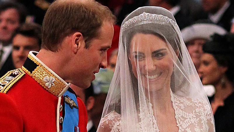 kate middleton si printul harry in ziua nunti, zambindu-si, imbracati in rochie de mireasa si el in costumul rosu