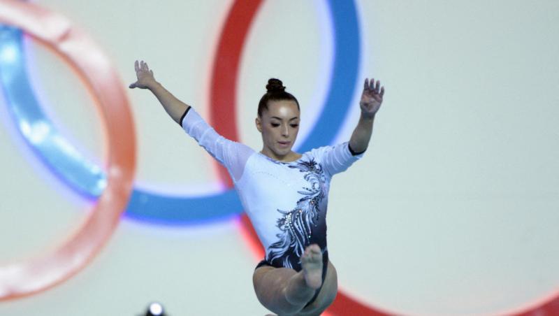 Larisa Iordache, în timpul unui exercițiu de gimnastică, într-un costum albastru