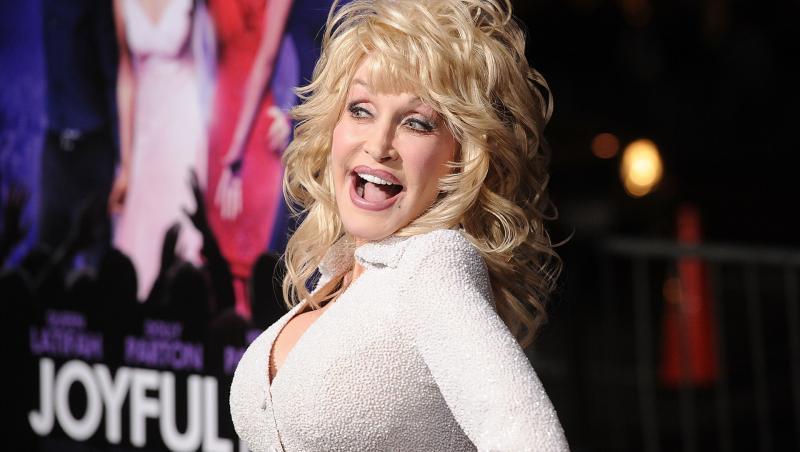 Dolly Parton pe covorul roșu la premiera filmului Joyful Noise, în 2012, în Los Angeles. E îmbrăcată într-o rochie albă, mulată, păr blond