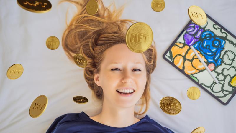 fata blonda intinsa pe un pat, cu banuti aurii in jurul capului pe care scris NFT