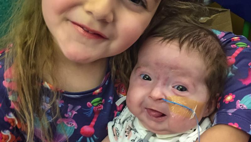 Isla Kilpatrick-Screaton când era bebeluș, îmbrăcată într-o bluză albă cu model albastru, și sora ei mai mare, îmbrăcată într-o bluză albastru, cu motive roz