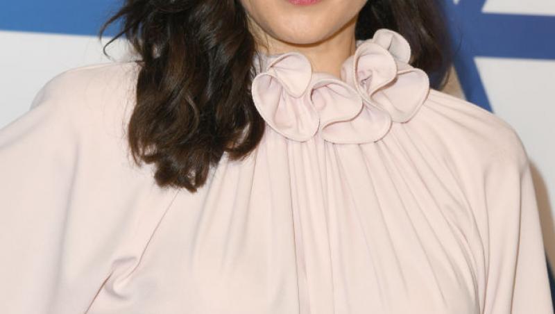 Rachel Weisz, îmbrăcată într-o rochie crem, cu părul desprins și o mână în șold